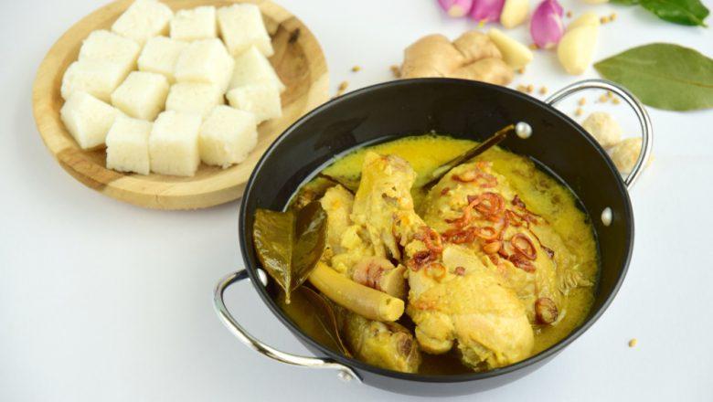 Lontong opor ayam kemangi disajikan di atas meja putih.