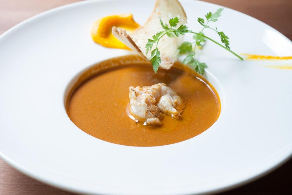 Masakan lobster bisque disajikan dalam piring mangkuk.
