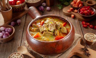 Resep Soto Sapi Santan disajikan dalam mangkuk tanah liat.