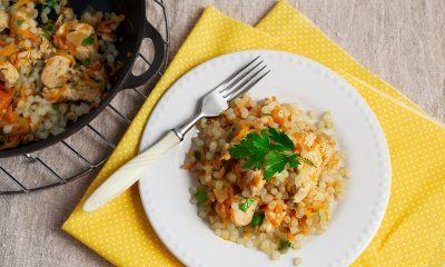 nasi goreng beras shirataki dengan topping potongan ayam dan wortel di atas piring putih