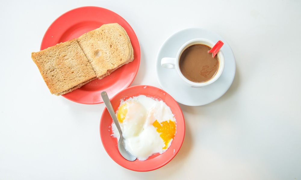 Kopi, roti bakar, dan telur setengah matang disajikan.